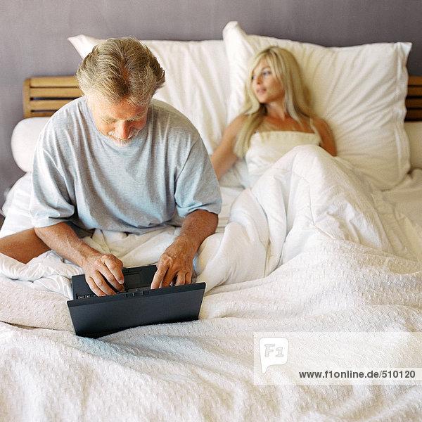 Paar im Bett  Mann mit Laptop