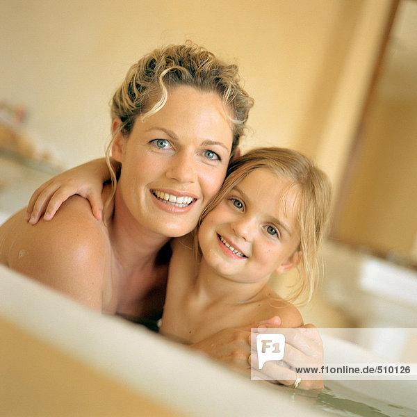 Frau und Mädchen in der Badewanne  lächelnd  Portrait