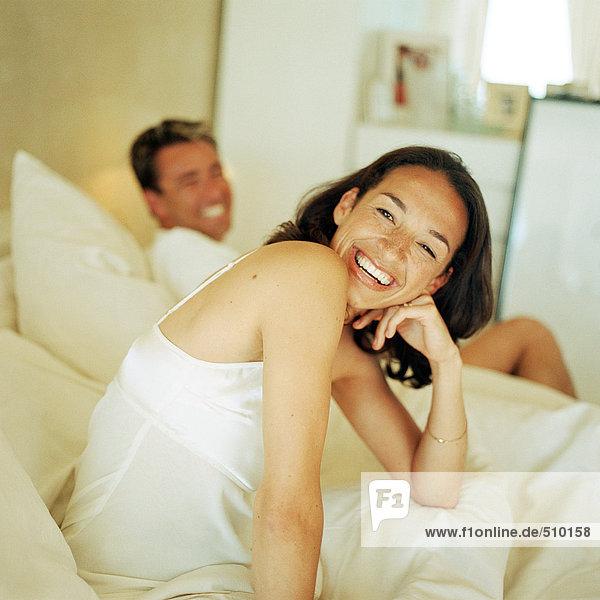 Mann und Frau auf dem Bett  lächelnd