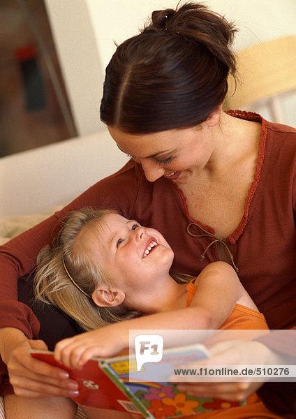 Mutter und Tochter lesen Buch  lächelnd