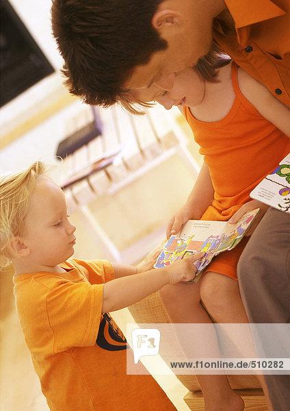 Vater und Kinder lesen Buch  Nahaufnahme