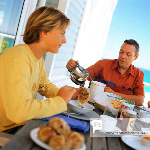 Teenager Junge und Vater beim Frühstück im Freien