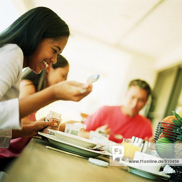 Teenager-Mädchen am Tisch mit Vater  unscharf