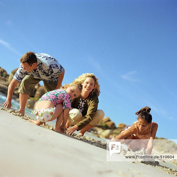 Paar und Kinder beim Graben im Sand  Portrait