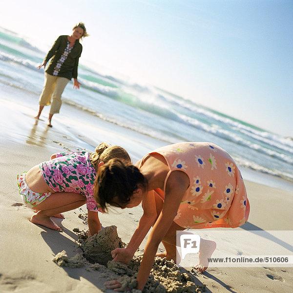 Frau geht am Strand spazieren  Kinder graben im Sand