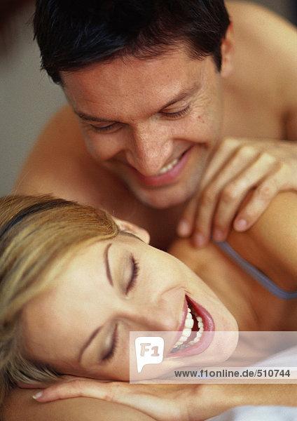 Paar auf dem Bett liegend  lächelnd
