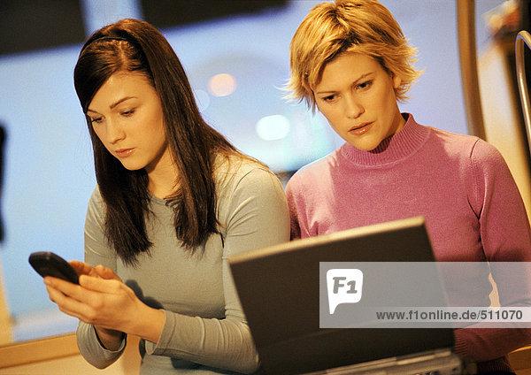Zwei junge Frauen  eine mit Laptop  eine mit Telefon