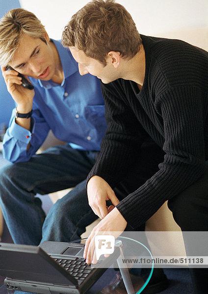 Zwei junge Männer  einer mit Laptop  einer mit Handy.