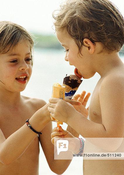 Zwei Kinder teilen sich ein Eis  Porträt. Zwei Kinder teilen sich ein Eis, Porträt.