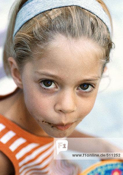 Kleines Mädchen mit Schokolade im Gesicht  Blick in die Kamera  Porträt. Kleines Mädchen mit Schokolade im Gesicht, Blick in die Kamera, Porträt.