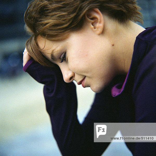 Profil der jungen Frau mit dem Kopf auf der Hand