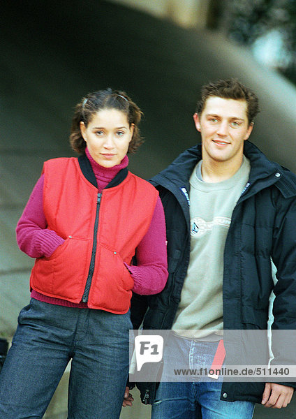 Young man and woman standing side by side wearing winter clothes