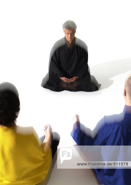 Menschen auf dem Boden sitzend  meditierend  verschwommen