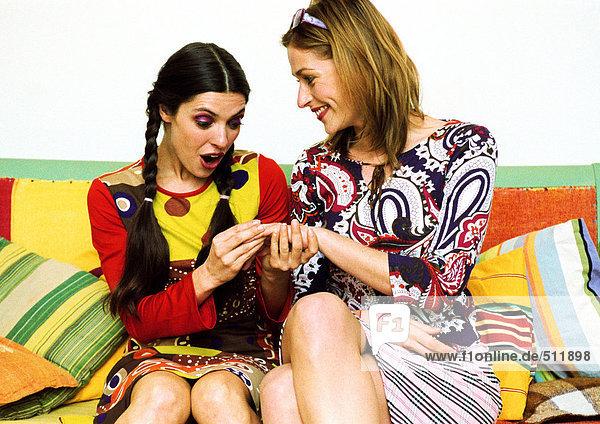 Zwei junge Frauen sitzen auf dem Sofa  eine zeigt die andere Hand.