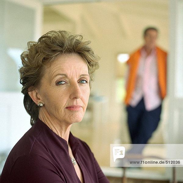 Reife Frau mit Blick auf die Kamera  Ehemann im Hintergrund  Portrait