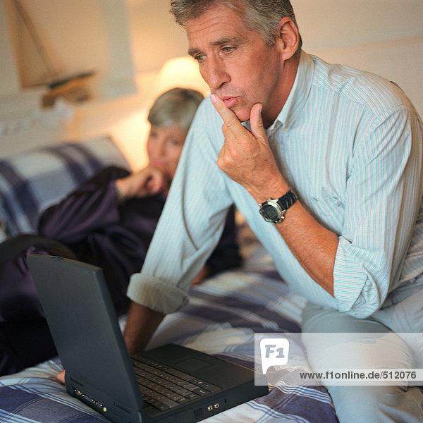 Erwachsener Mann mit Laptop im Bett  Frau im Hintergrund