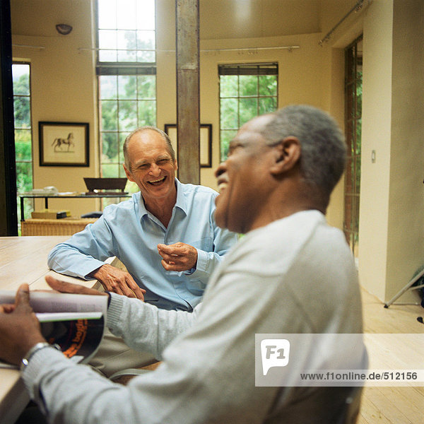 Two mature men sitting at table  laughing