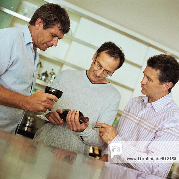 Drei Männer betrachten Weinflasche
