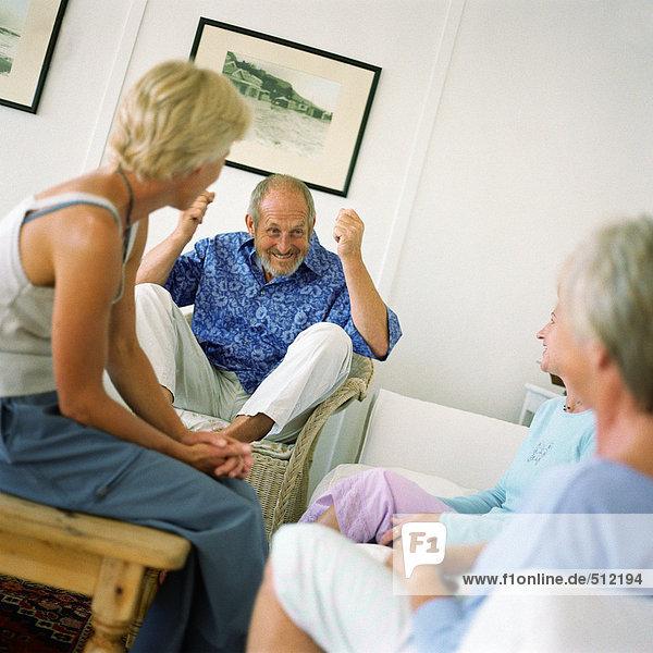 Vier Personen sitzen in einem Raum  Mann hebt Arme und Knie