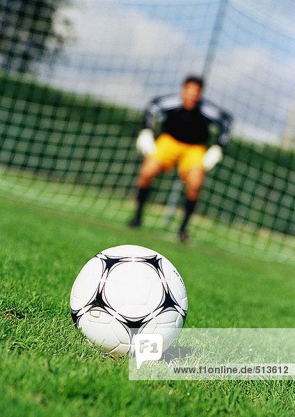 Soccerball im Vordergrund  Torwart vor dem Tornetz  verschwommen im Hintergrund