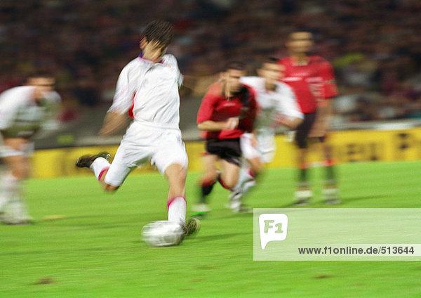 Fußballspieler im Begriff  den Ball zu kicken  vier Spieler im Hintergrund  verschwommen.