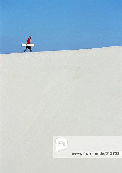 Mann  der den Dünenkamm mit Sandbrett entlanggeht