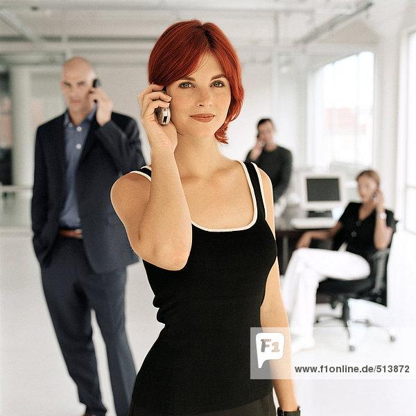 Geschäftsleute mit Mobiltelefonen im Büro  Portrait