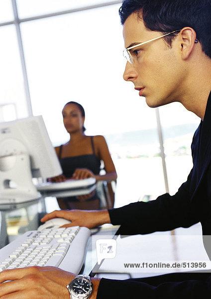Geschäftsmann und Geschäftsfrau am Schreibtisch  Seitenansicht des Mannes im Vordergrund