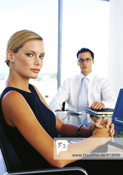 Businessman and woman sitting in office  portrait