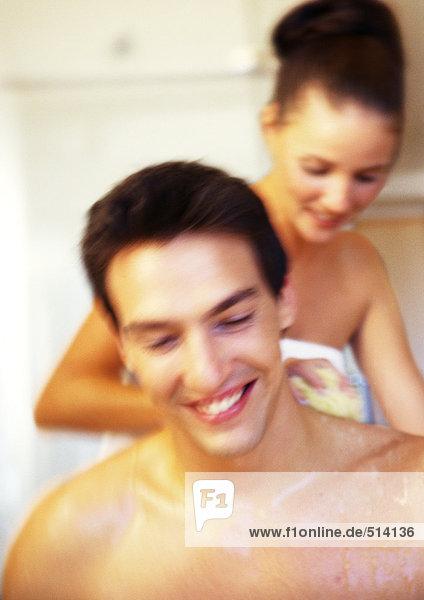 Frau wäscht nackt den Rücken des Mannes