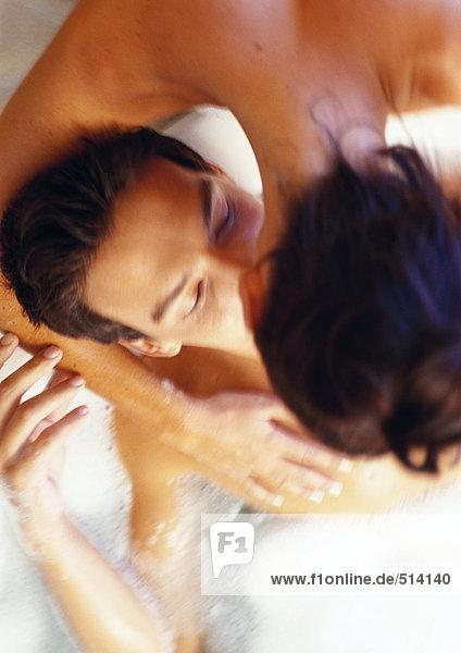 Frau beugt sich vor  küsst Mann im Bad