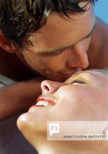 Paar lächelnd  Mann im Begriff  die Stirn der Frau zu küssen  Nahaufnahme