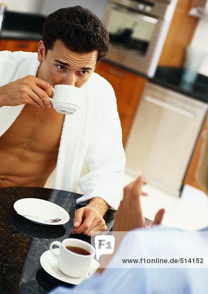 Mann und Frau am Tisch sitzend  Mann trinkt aus Teetasse  Teilansicht der Frau im Vordergrund