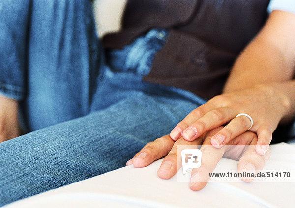Frauenhand auf Männerhand  Nahaufnahme