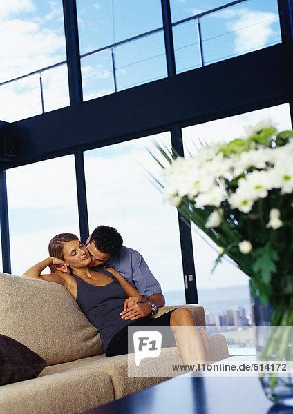 Mann küsst Frauenhals auf Sofa