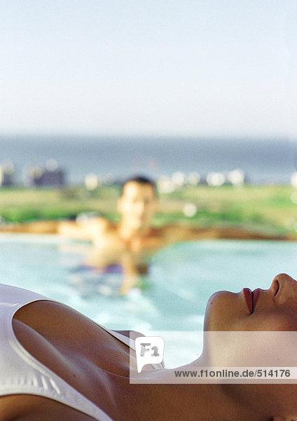 Frau im Badeanzug liegend  Mann im Pool im Hintergrund  Nahaufnahme