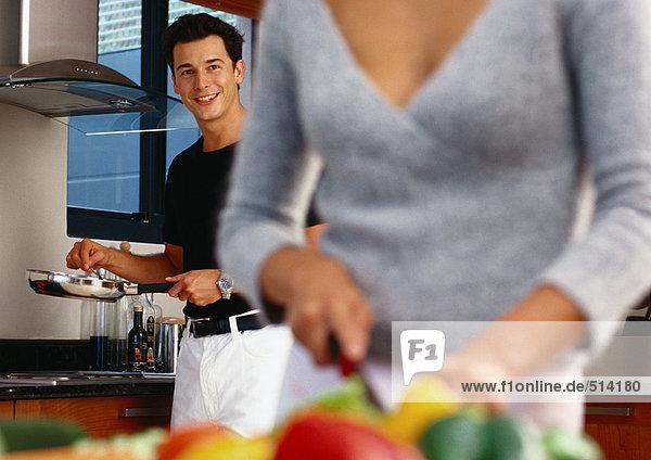 In der Küche  Mann hält Pfanne  Frau schneidet Gemüse in verschwommenen Vordergrund