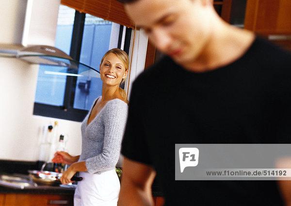 Frau in der Küche  lächelnd auf den Mann zu  im Vordergrund verschwommen.