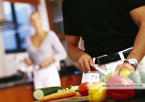 Mann schneidet Gemüse  Mittelteil  Frau steht im Hintergrund
