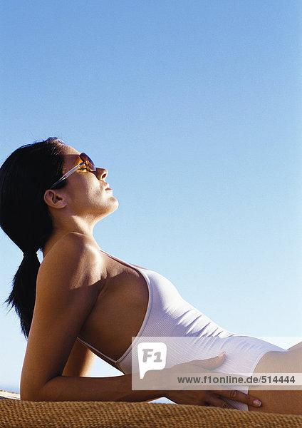 Frau im Badeanzug auf Ellenbogen lehnend  Seitenansicht