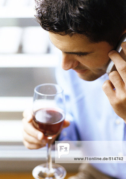 Man using cell phone  holding wine glass  close-up