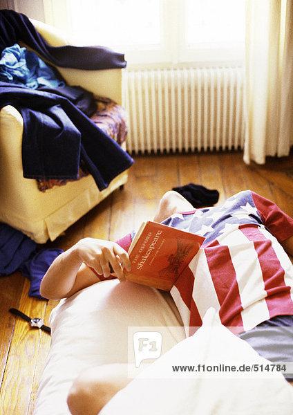 Mann auf dem Bett liegend mit Buch in der Hand