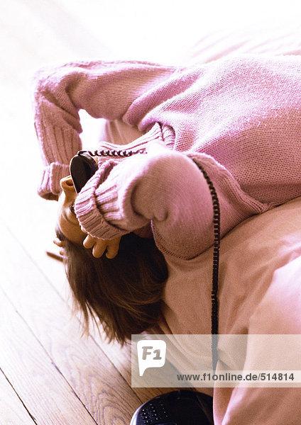 Frau auf dem Bett liegend mit Telefon in der Hand und Kopf hängend am Bett