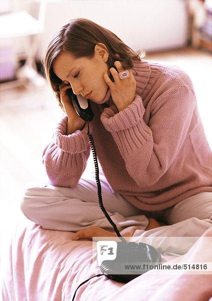 Frau auf dem Bett sitzend  telefonierend