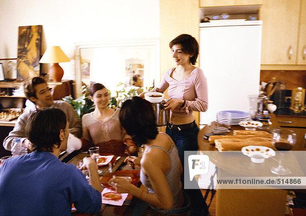 Vier Leute sitzen am Tisch  eine Frau bringt den Teller.