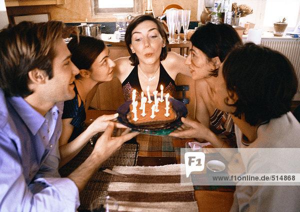 Vier Leute halten Kuchen  eine Frau bläst Kerzen aus.