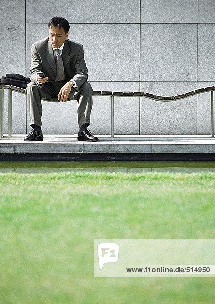 Geschäftsmann auf der Bank mit Blick auf das Handy