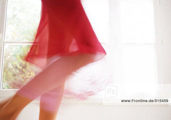 Frau walking vor Fenster, Unterteil, verschwommen Bewegung.