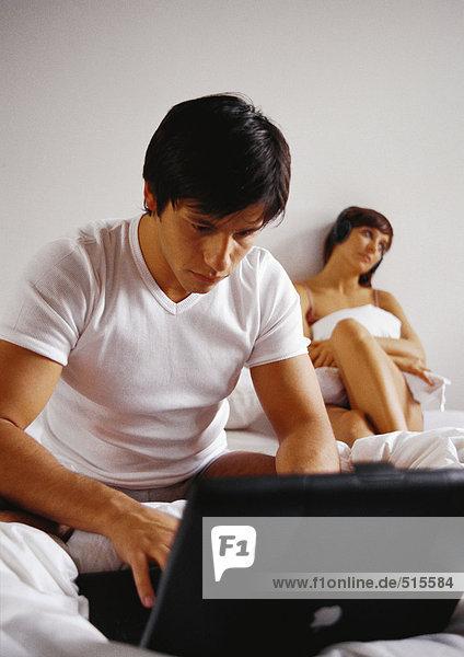 Mann arbeitet am Laptop im Bett  Frau im Hintergrund.