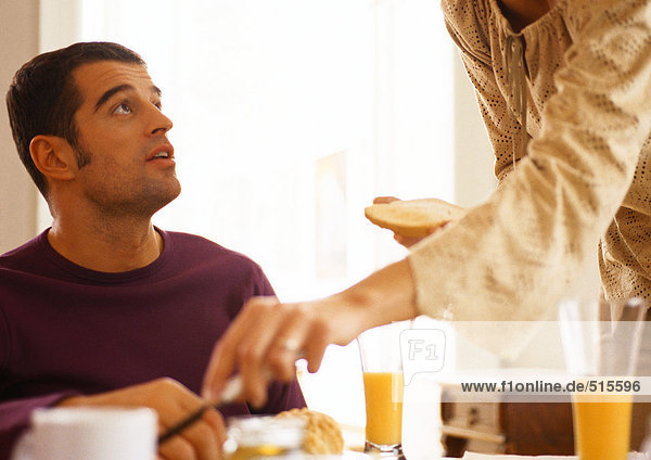 Frau mit Toast steht über dem Mann bei Tisch.